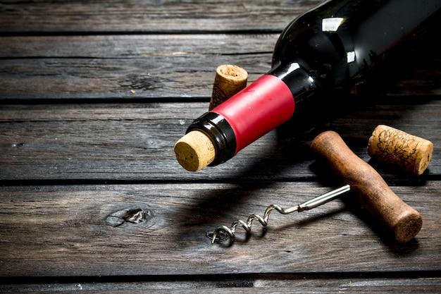 Eine flasche rotwein mit einem korkenzieher. auf einem hölzernen hintergrund.