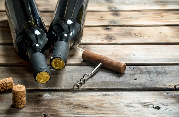 Eine flasche rotwein mit einem korkenzieher. auf einem holz.