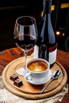 Eine flasche rotwein mit tasse kaffee und schokolade auf holztisch