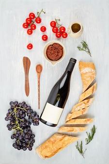 Eine flasche rotwein, trauben, brot und tomaten für die buffetparty. traditionelles französisch oder italienisch führt zu einer flachen lage. draufsicht