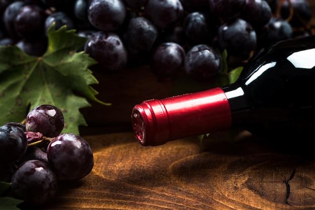 Eine flasche rotwein und frische weintrauben