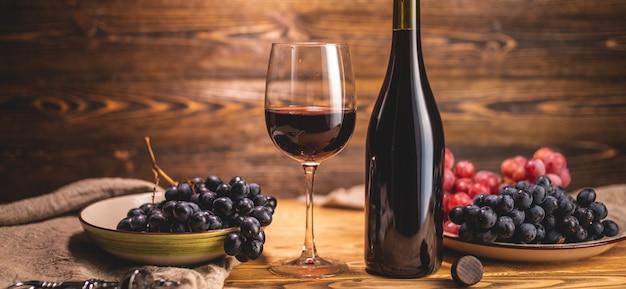 Eine flasche trockener rotwein mit einem glas und einer weintraube auf einem holztisch