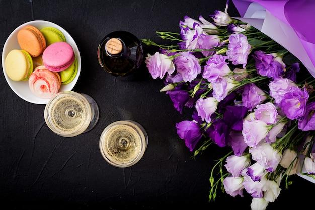 Eine flasche trockener weißwein und eine makrone. flach liegen. ansicht von oben.