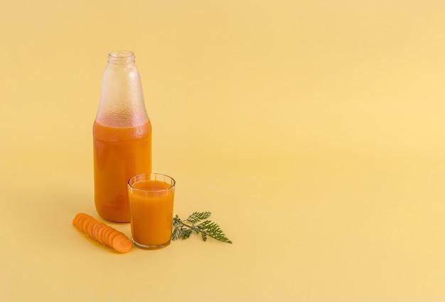 Eine flasche und ein glas karottensaft neben den gehackten karotten