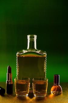Eine flasche und ein glas mit alkohol und lippenstift und ein parfüm