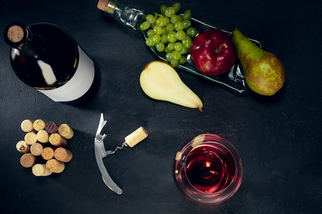 Eine flasche und ein glas rotwein mit früchten auf dunklem steinhintergrund