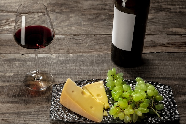 Eine flasche und ein glas rotwein mit früchten auf holzhintergrund