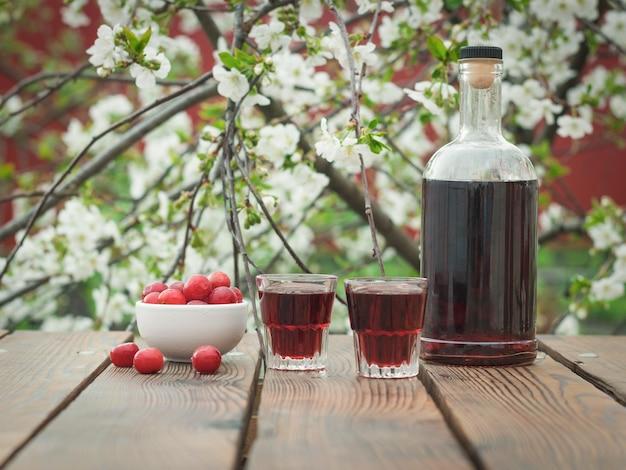 Eine flasche und gläser mit kirschlikör und kirschbeeren