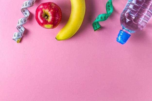Eine flasche wasser, ein apfel, eine banane und ein maßband. sport und diät-konzept. sport und gesunder lebensstil. copyspace hintergrund