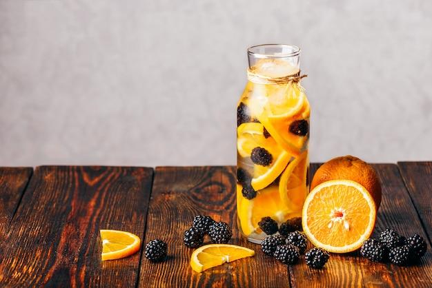 Eine flasche wasser mit geschnittener roher orange und frischer brombeere. zutaten auf holztisch.