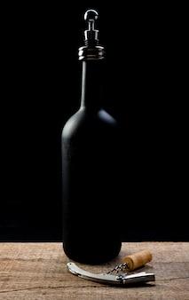 Eine flasche wein auf einem rustikalen holztisch mit einem korkenzieher und einem korken und die flasche hat einen weindeckel.