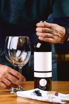 Eine flasche wein und gläser auf dem tisch vor dem hintergrund eines wein-shakafa. s.