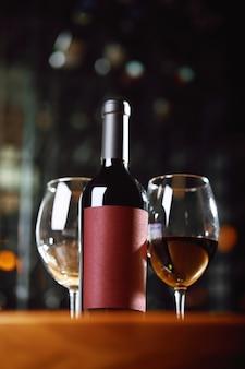 Eine flasche wein und gläser auf dem tisch vor dem hintergrund eines wein-shakafa.