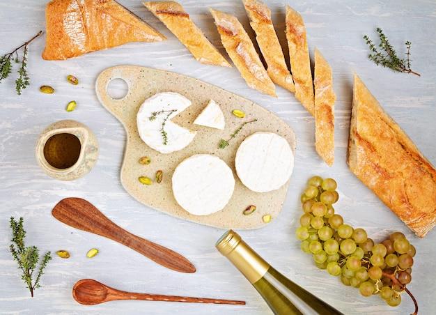 Eine flasche weißwein, käse, brot und tomaten für die buffetparty. traditionelles französisch oder italienisch führt zu einer flachen lage. draufsicht