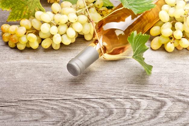 Eine flasche weißwein und frische trauben