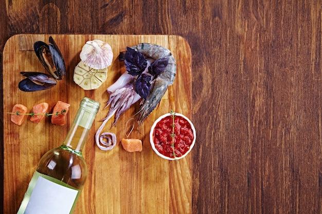Eine flasche weißwein und rote sauce auf geschnittenem brett und holztisch mit meeresfrüchten - muschel, garnele, tintenfisch, basilikum und kleine lachsstücke mit kräutern