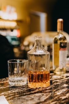 Eine flasche whisky und ein glas auf der bartheke.