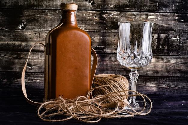 Eine flasche whisky und leeres weinglas auf einem schwarzen holz