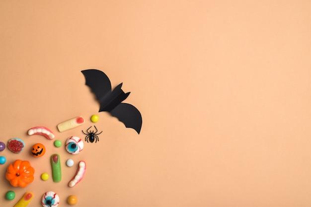 Eine fledermaus fliegt und dahinter verschiedene süßigkeiten auf orangefarbenem hintergrund mit einem platz für text. hintergrund für den halloween-urlaub. flaches layout, draufsicht, ein ort zum kopieren. fröhliches halloween.