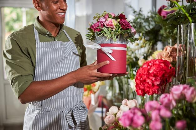 Eine floristin, die einen roten rosentopf mit anderen blumen zwischen die glasvasen stellt