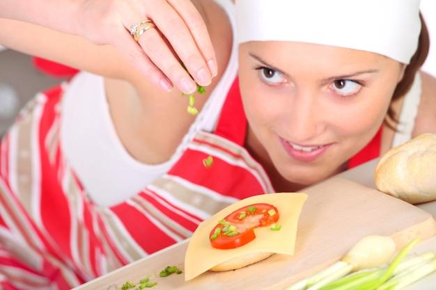Eine fokussierte frau, die ein sandwich mit petersilie würzt, konzentriert sich auf sandwich