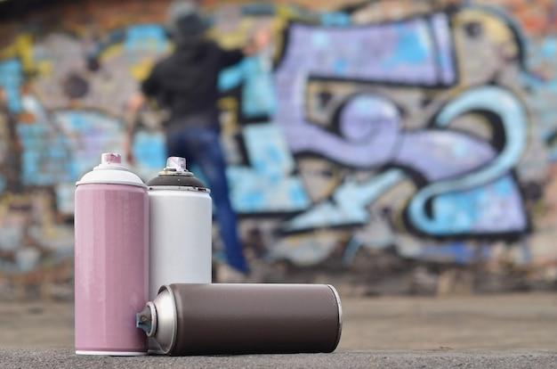 Eine fotografie einer bestimmten anzahl von farbdosen gegen die graffiti