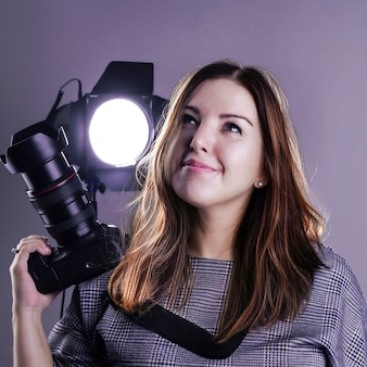 Eine fotografin in einem studio mit spiegelreflexkamera und lichtequipment blickt verträumt nach oben. das konzept - in träumen, ein großartiger fotograf zu werden