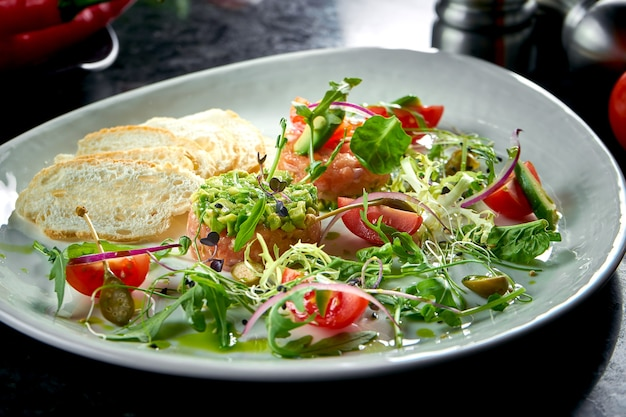 Eine französische vorspeise vor dem hauptgericht - lachssteak-tartar mit avocado, kirschtomate und croutons, serviert auf einem weißen teller. restaurant essen. sicht von oben