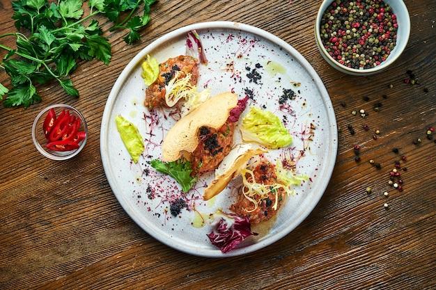 Eine französische vorspeise vor dem hauptgericht - lachssteak-tartar mit schwarzem kaviar, frischkäse und croutons, serviert auf einem weißen teller. restaurant essen. sicht von oben