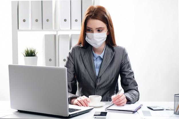 Eine frau an einem schreibtisch in einer medizinischen schutzmaske im büro, das am computer arbeitet.