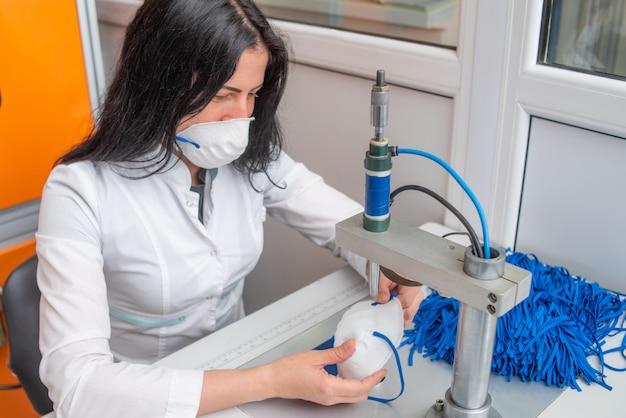 Eine frau arbeitet an einer maschine zur herstellung von medizinischen masken mit nanofaser und lötschleifen mit ultraschall.