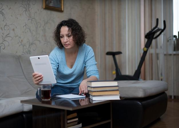 Eine frau arbeitet zu hause hinter einem tablet.