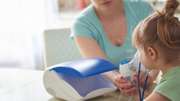 Eine frau atmet ein kind zu hause ein. bringt die verneblermaske an sein gesicht. atmet den dampf des medikaments ein. das mädchen atmet durch eine maske.
