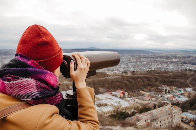 Eine frau auf der aussichtsplattform schaut durch ein fernglas auf eine stadt in den bergen.