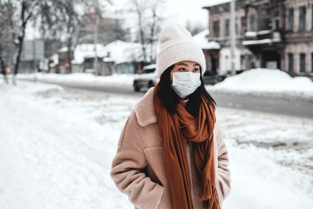 Eine frau auf der straße im winter schützt die atemwege vor der coronavirus-epidemie