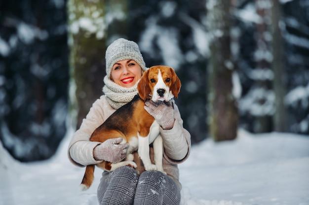 Eine frau auf einem spaziergang mit ihrem hund im winterwald. herrin und hundespiel im verschneiten wald.