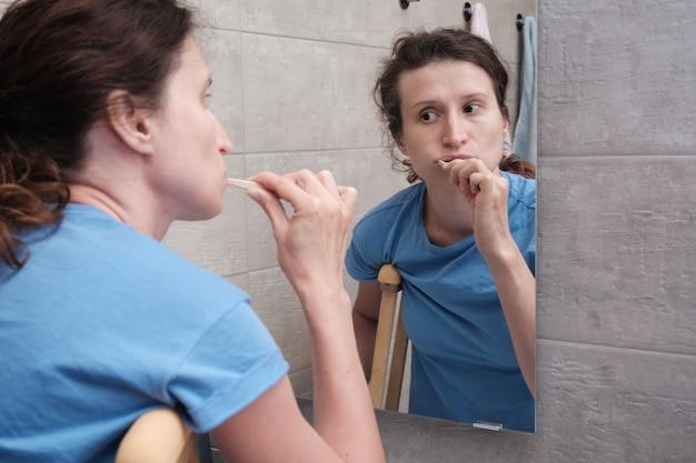 Eine frau auf krücken mit gebrochenem bein putzt sich im badezimmer die zähne