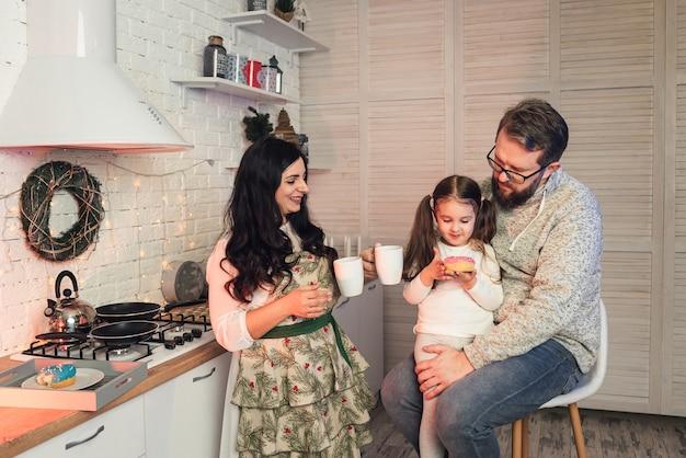 Eine frau behandelt ihre tochter und ihren ehemann mit tee und donuts