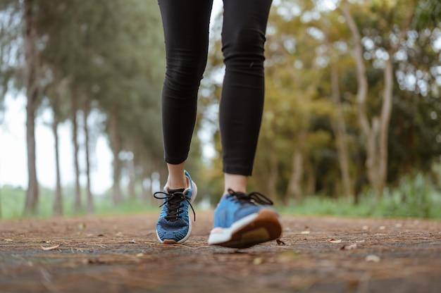Eine frau beim joggen im naturpark. beine hautnah.