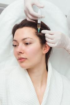 Eine frau bekommt einen schuss in den kopf in einer kosmetikklinik mesotherapie für haarwuchs