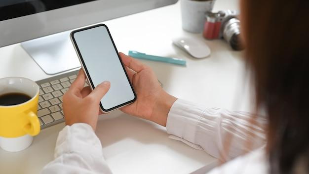 Eine frau benutzt ein weißes smartphone mit leerem bildschirm, während sie vor einem computermonitor sitzt