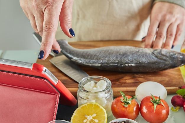 Eine frau benutzt eine folie mit dem finger auf dem tablet-bildschirm, während sie gemäß dem online-tutorial für virtuelle meisterklassen kocht, und betrachtet ein digitales rezept, während sie in der küche eine gesunde mahlzeit zubereitet