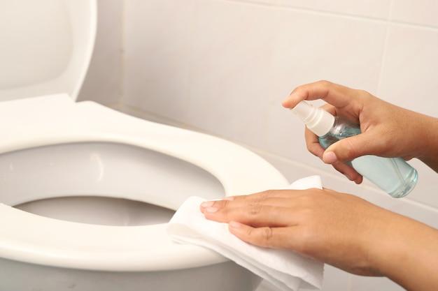 Eine frau benutzt toilettenpapier zum reinigen des badezimmers und alkohol.