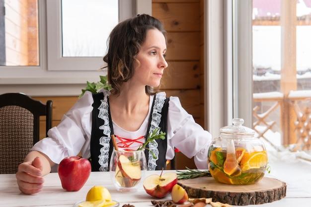Eine frau bereitet am tisch am fenster gesunden kräutertee mit früchten zu. das konzept von gesundheit und antivirus.