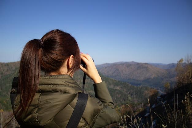 Eine frau betrachtet die wunderschöne landschaft der berge mit einem fernglas von der aussichtsplattform aus
