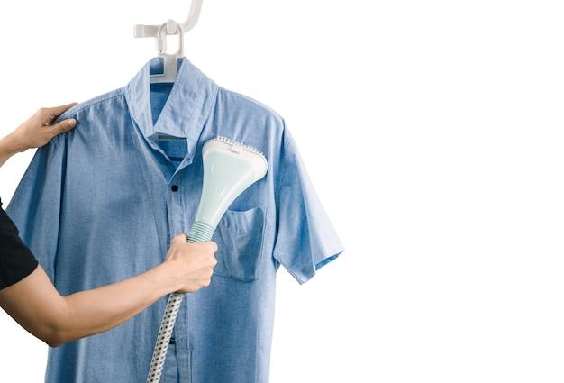 Eine frau bügelt kleidung mit dampfbügeleisen eine frau bügelt kleidung mit dampfbügeleisen weißen hintergrund