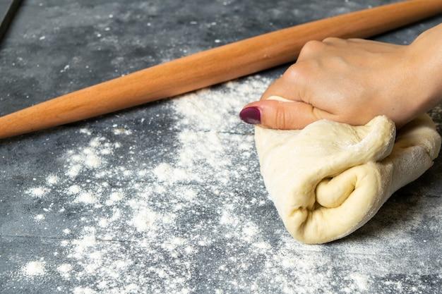 Eine frau der vorderansicht, die teig mit mehl auf grauem schreibtischgebäckdamenfutter macht