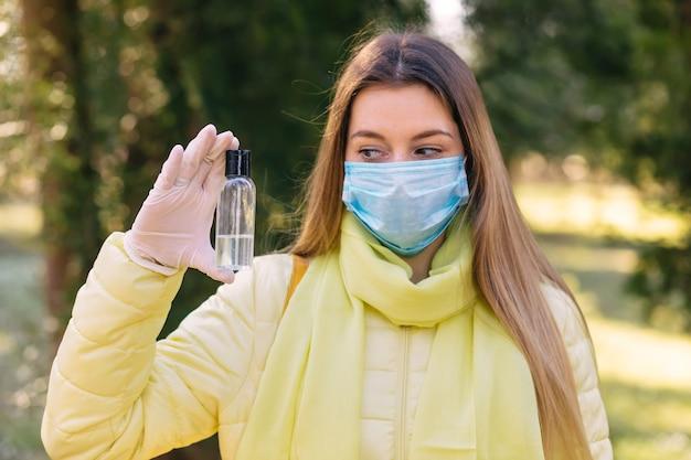 Eine frau desinfiziert die hände mit einem spray in der hand. sie trägt eine medizinische gesichtsschutzmaske, die vor dem virus schützt. covid-19