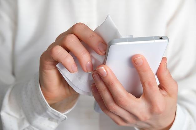 Eine frau desinfiziert ein mobiltelefon mit einer serviette, die ein alkoholisches antibakterielles mittel enthält.