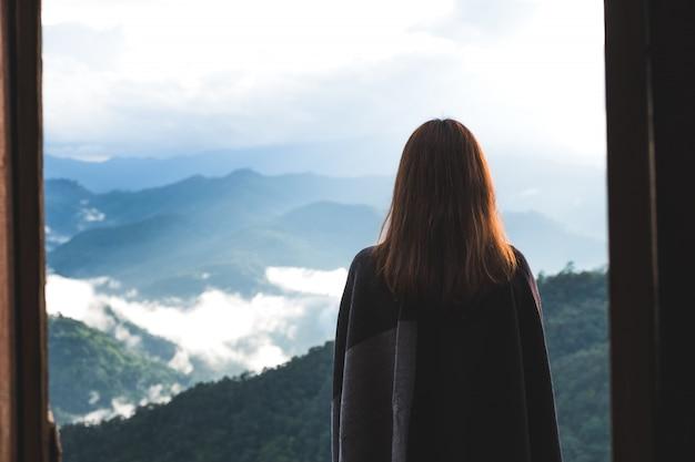 Eine frau, die allein auf balkon steht und berge am nebligen tag mit blauem himmel betrachtet